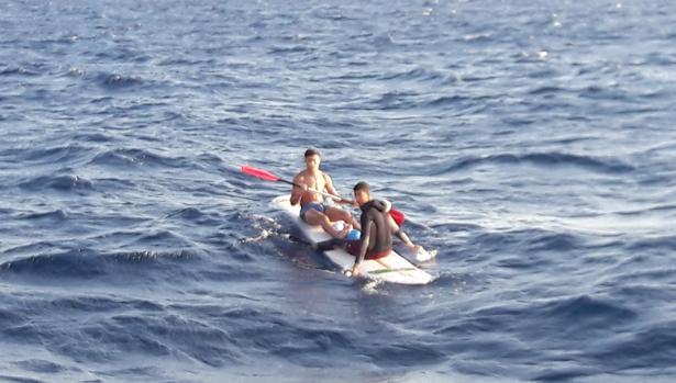 Inmigrantes navegan sobre tablas de surf para llegar su destino